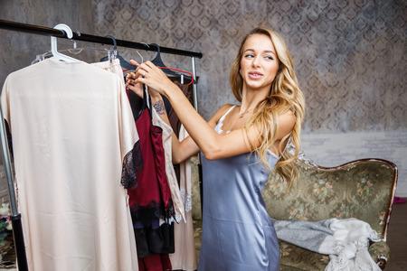 Beautiful girl blonde in underwear and pajamas posing in bedroom, interior