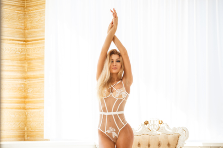 Beautiful girl blonde fitness posing in lingerie in the bright hotel apartments