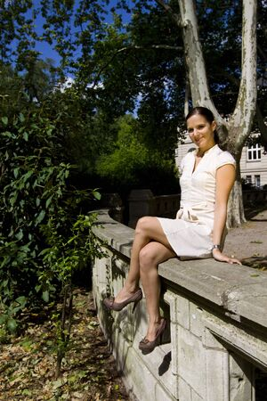 legs crossed: model outdoor fashion portrait in the park