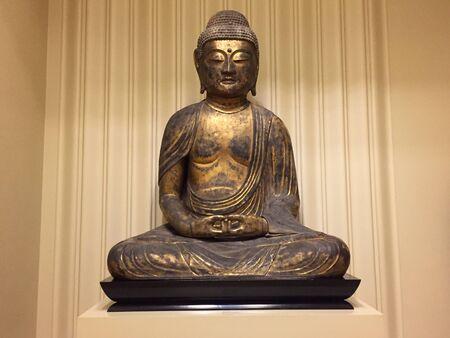 Statue of Buddha sitting crosslegged and meditating