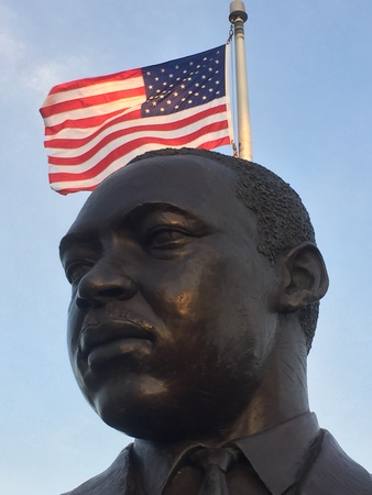 Statue of Dr. Martin Luther King Jr. with American flag .