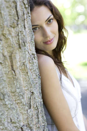 environmentalist: Woman leaning against a tree