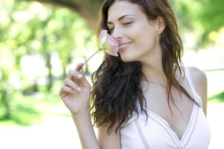 environmentalist: Woman smelling a flower