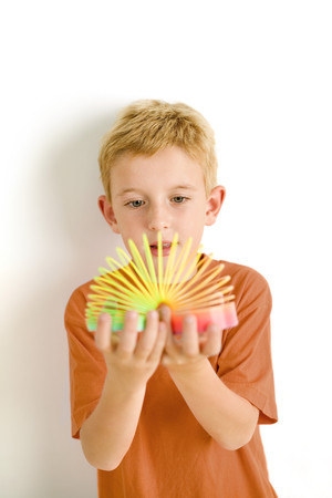 Boy playing with slinky toy LANG_EVOIMAGES
