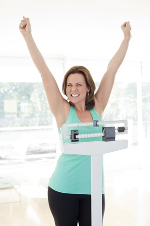 herself: Successful weight loss.Happy woman weighing herself