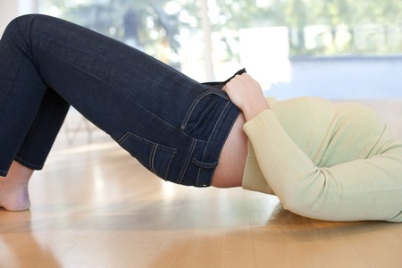Overweight woman struggling to do her jeans up LANG_EVOIMAGES