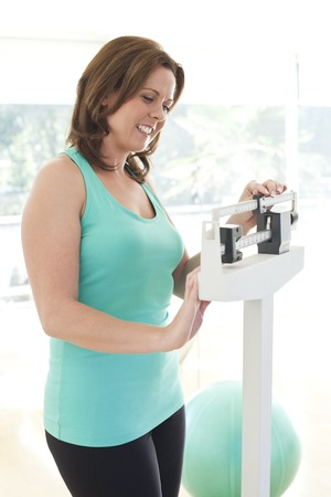 Woman weighing herself LANG_EVOIMAGES