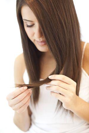 front end: Split ends.Teenage girl examining her split ends