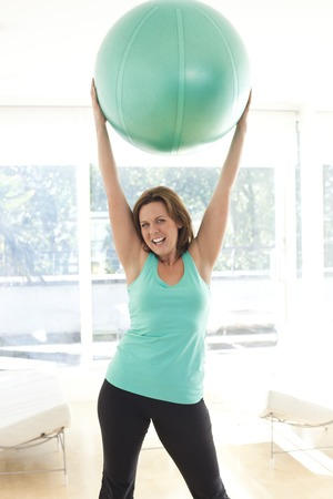Woman exercising with an exercise ball LANG_EVOIMAGES