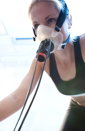 static bike: MODEL RELEASED.Performance testing.Athlete riding an exercise bike while her performance and oxygen consumption are measured