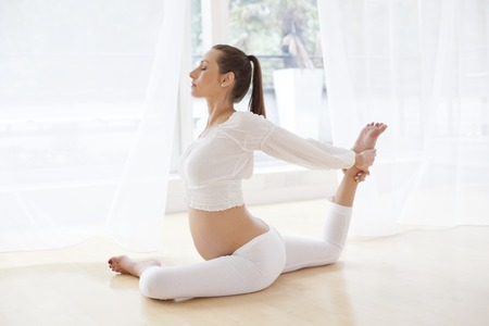 MODEL RELEASED. Pregnant woman practicing yoga