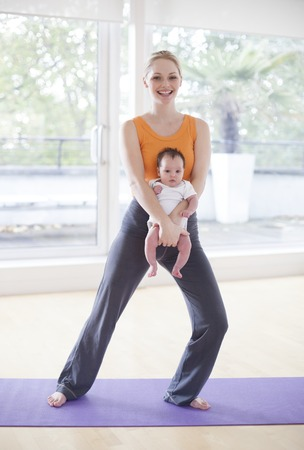 MODEL RELEASED. Mother and her 5 week old daughter doing yoga LANG_EVOIMAGES