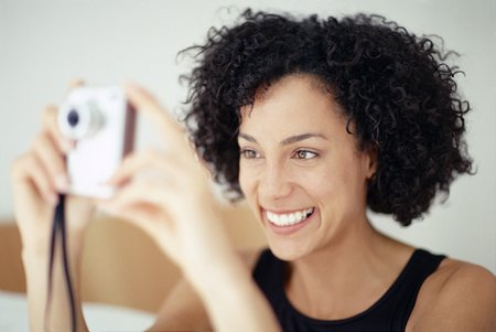 MODEL RELEASED. Woman taking a photograph LANG_EVOIMAGES