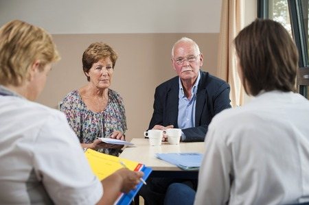 mixed age range: MODEL RELEASED. Hospital consultation. Care team meeting with a patient and her partner