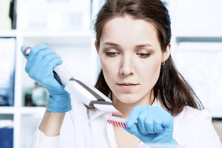blood transfer: MODEL RELEASED. Haematology lab. Laboratory assistant using a multipipette to transfer blood samples