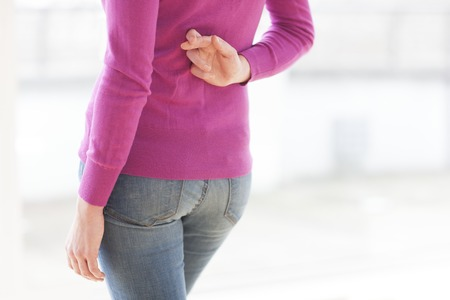 hope indoors luck: Fingers crossed behind womans back LANG_EVOIMAGES
