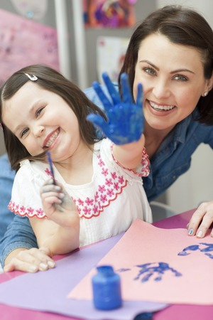 PROPERTY RELEASED. MODEL RELEASED. Young girl with her hand painted blue with her mother LANG_EVOIMAGES