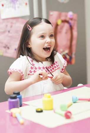 PROPERTY RELEASED. MODEL RELEASED. Young girl playing with paints and brushes