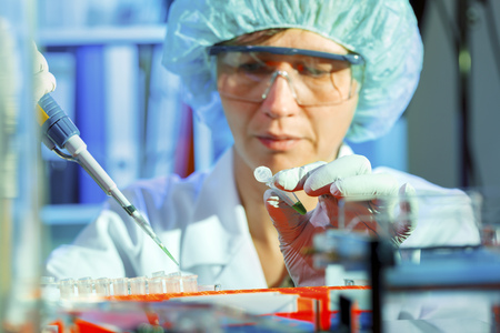 accurately: Lab technician using a pipette