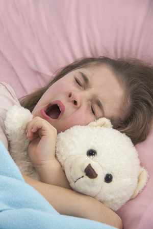 Girl yawning in bed holding teddy bear LANG_EVOIMAGES