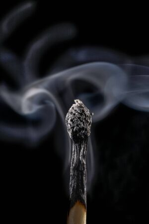 endings: Burnt matchstick and smoke against a black background LANG_EVOIMAGES
