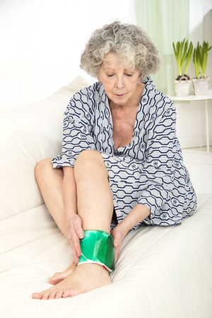 compress: Woman with a cold compress on ankle
