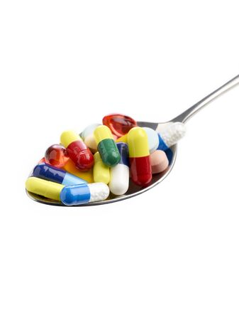 Spoon full of tablets and capsules against a white background