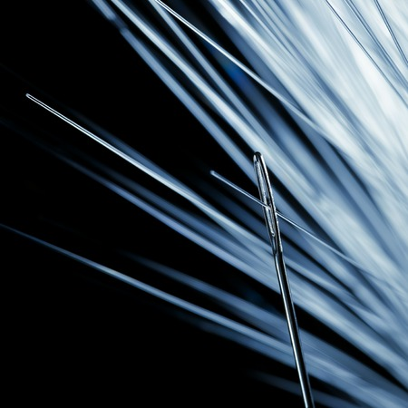 accurately: Fibre optic being thread through a needle, close up