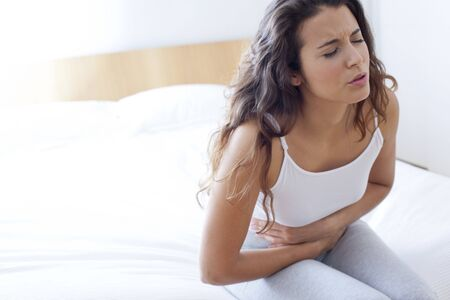 abnormal: Woman on bed with cramps LANG_EVOIMAGES