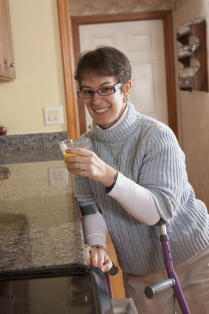 cerebral palsy: Woman using crutches in her kitchen