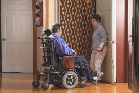 cerebral palsy: Disabled couple entering a home elevator LANG_EVOIMAGES