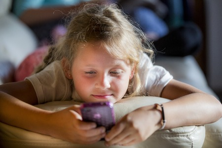 Girl lying on front using a smartphone LANG_EVOIMAGES
