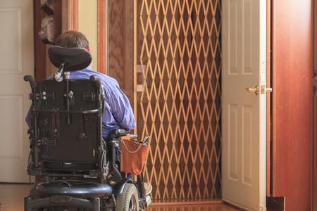 cerebral palsy: Disabled man entering a home elevator LANG_EVOIMAGES