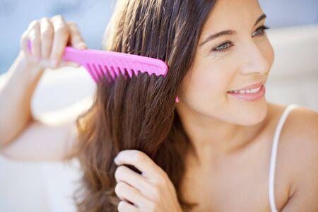 comb: Woman combing her hair