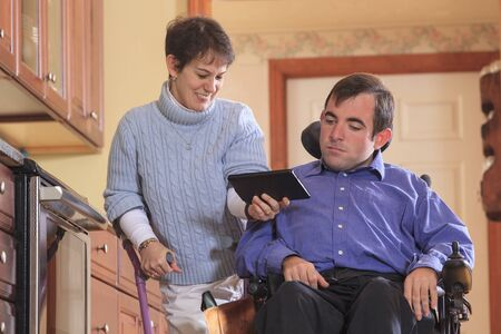 cerebral palsy: Disabled couple using tablet LANG_EVOIMAGES