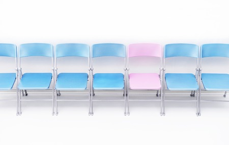 One pink chair in a row of blue chairs LANG_EVOIMAGES