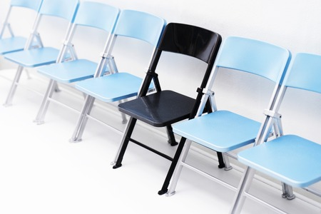 One black chair in a row of blue chairs