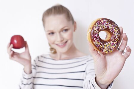 pregnant women donuts: Pregnant woman holding apple and doughnut