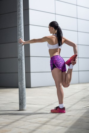 Woman stretching leg muscles LANG_EVOIMAGES