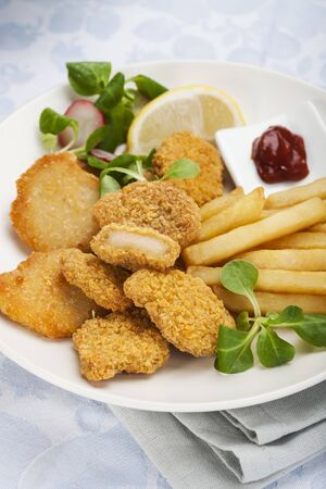 Chicken nuggets, chips and salad