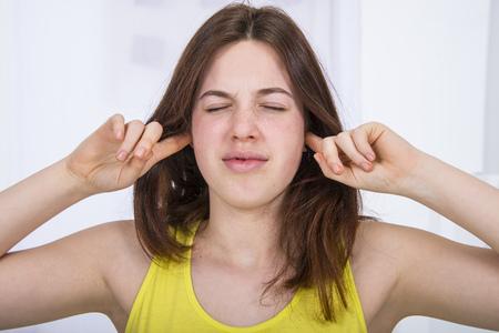 Teenage girl with fingers in ears
