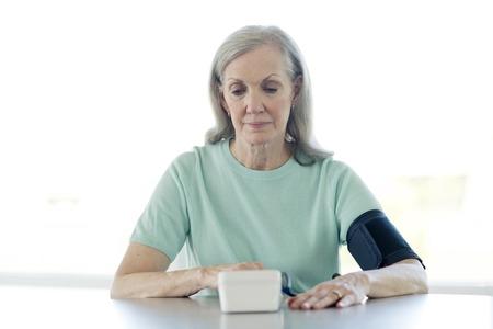 Senior woman taking her own blood pressure