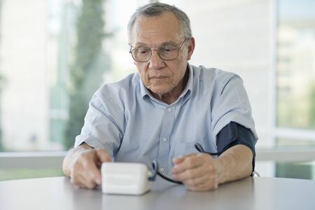 Senior man taking his own blood pressure