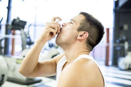 Young man using inhaler