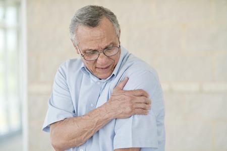 Senior man holding his left arm in pain