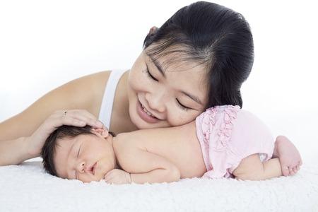 Mother stroking newborn baby girls head