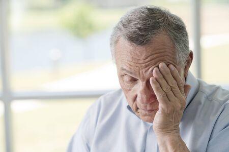 Senior man rubbing face