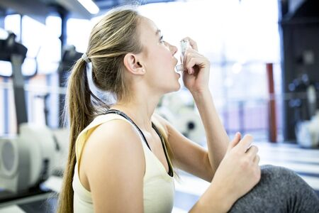 Young woman using inhaler LANG_EVOIMAGES