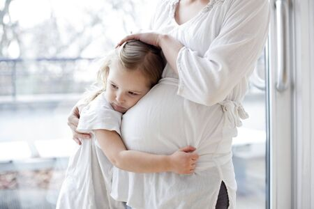 Pregnant mother with arms around daughter LANG_EVOIMAGES