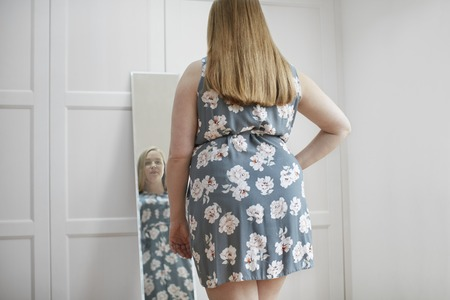 mirror image: Young woman looking at reflection in mirror